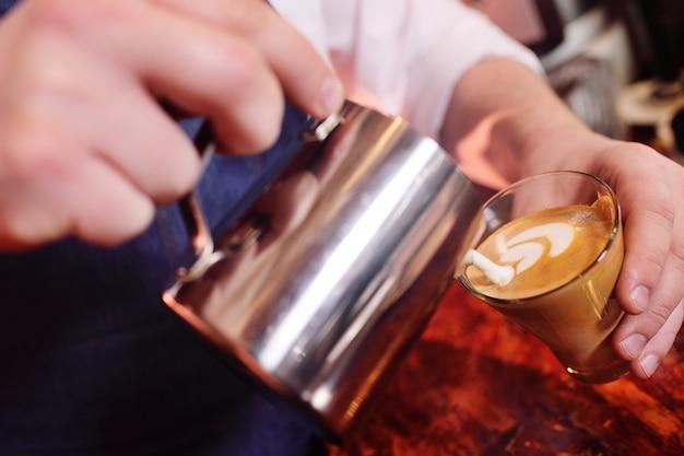 Café barman prepara café com um padrão na espuma ou latte-art Foto Premium