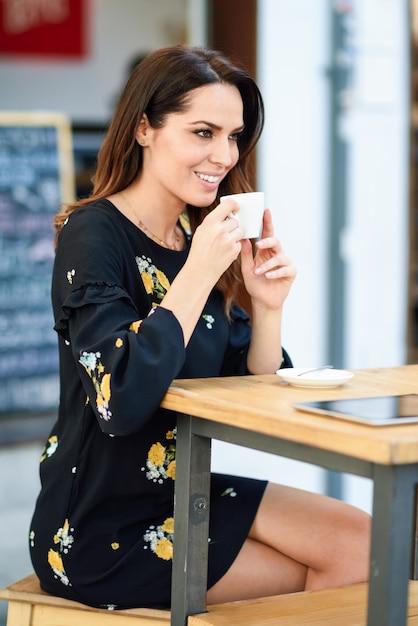 Café bebendo da mulher de meia idade em uma barra urbana do café. Foto Premium