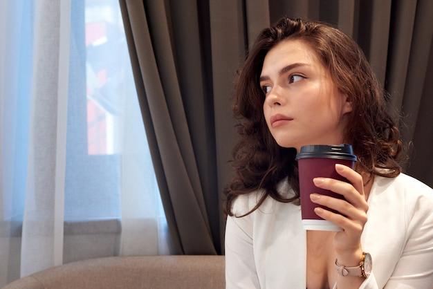 Café beber pensativo jovem linda garota em um café Foto Premium