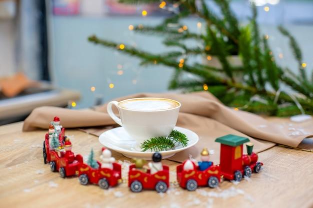 Café cappuccino delicioso fresco festivo de manhã em uma xícara de cerâmica branca em cima da mesa de madeira Foto Premium