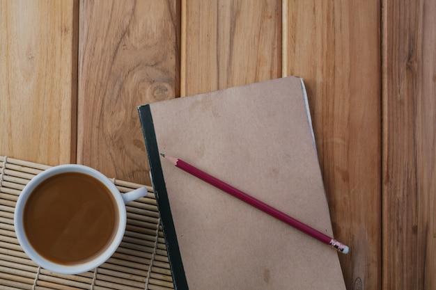 Café colocado ao lado do livro no chão de madeira marrom. Foto gratuita