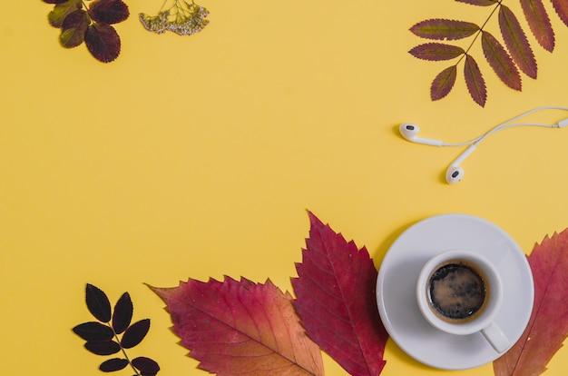 Café com herbário e fones de ouvido no fundo amarelo. outono. Foto Premium