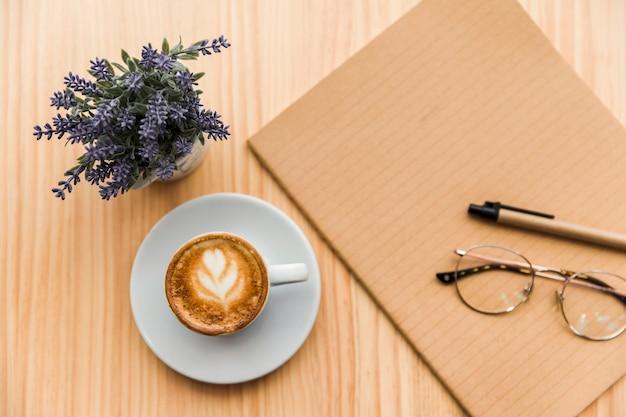 Café com leite, artigos de papelaria e flor de lavanda na mesa de madeira Foto gratuita