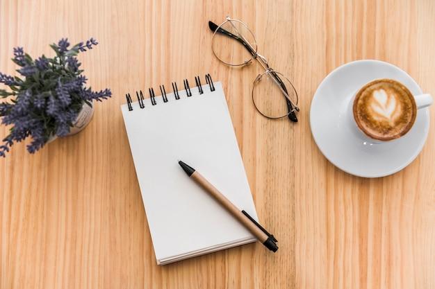 Café com leite, bloco de notas em espiral, espetáculos e flor de lavanda em fundo de madeira Foto gratuita