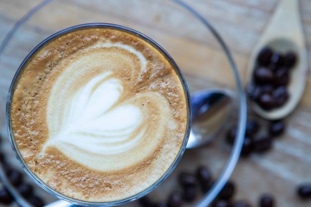 Café com leite coração, feijão em uma mesa de madeira Foto Premium