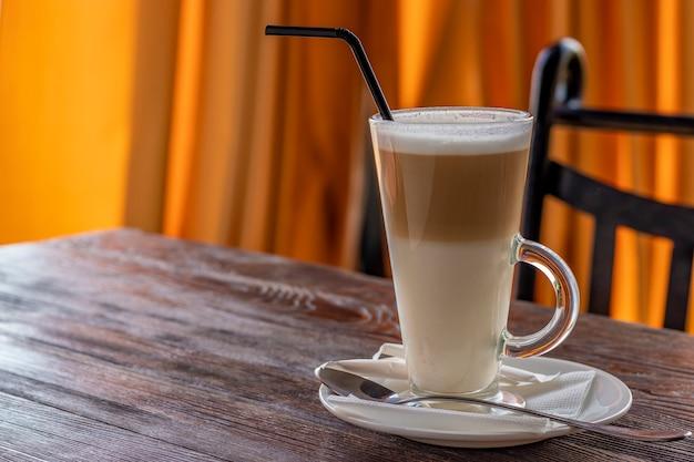 Café com leite em um copo sobre uma mesa de madeira, copie o espaço Foto Premium