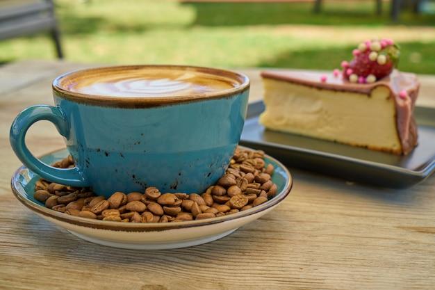 Café com leite, grãos de café e cheesecake na mesa de madeira Foto Premium