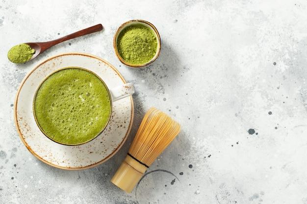 Café com leite matcha chá verde em uma xícara com creme. Foto Premium
