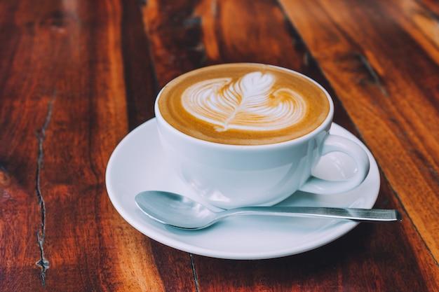 Café com leite na mesa de madeira na cafeteria Foto Premium