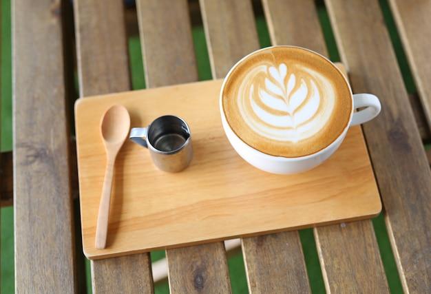 Café com leite quente com padrão de corações e xarope na mesa de madeira Foto Premium