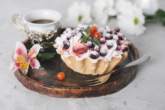 Café com torta de frutas saborosas e flores na bandeja de madeira Foto gratuita