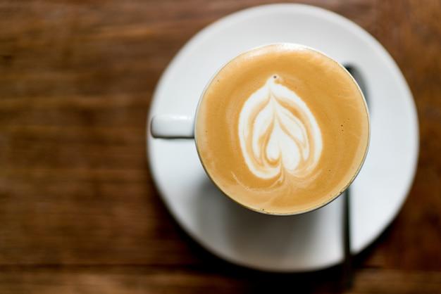 Café da arte do latte da vista superior em de madeira. espuma da arte do latte da forma do coração. s Foto Premium