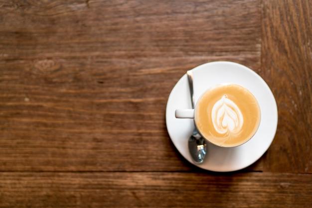 Café da arte do latte da vista superior em de madeira. espuma da arte do latte da forma do coração. Foto Premium