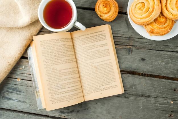 Café da manhã aconchegante na primavera ou no chá do outono, scones recém-assados e buquê de margaridas e livro fascinante do campo. copie o espaço Foto Premium
