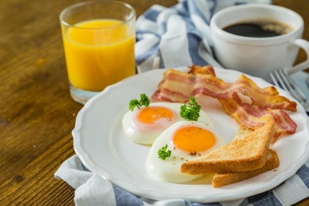 Café da manhã americano com ovos fritos, bacon, torradas, panquecas, café e suco Foto Premium