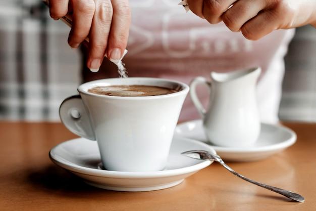 Café da manhã. close up das mãos das mulheres com copo de café em um café. femininas, mãos, segurando, xícaras café, ligado, um, tabela madeira, em, um, café, cor vintage, tom Foto Premium