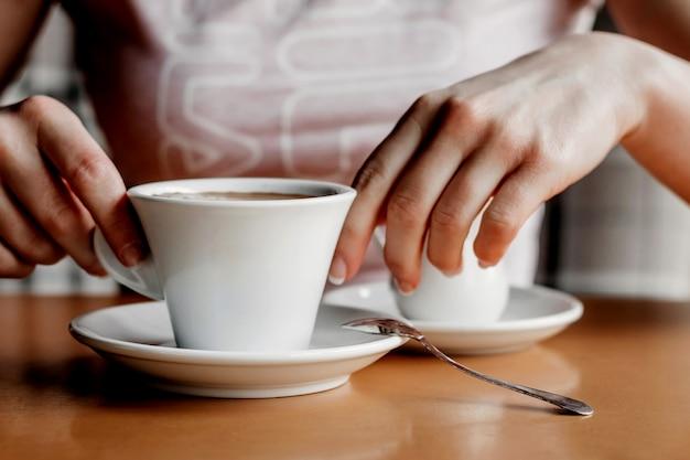 Café da manhã. close up das mãos das mulheres com copo de café em um café. Foto Premium