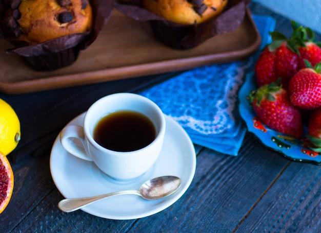 Café da manhã com café e chá com diferentes bolos e frutas em uma mesa de madeira Foto Premium