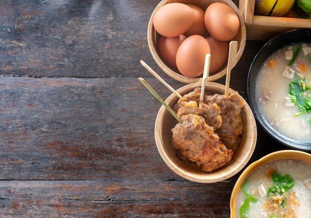 Café da manhã com carne de porco assada com ovos cozidos e mingau de arroz Foto Premium
