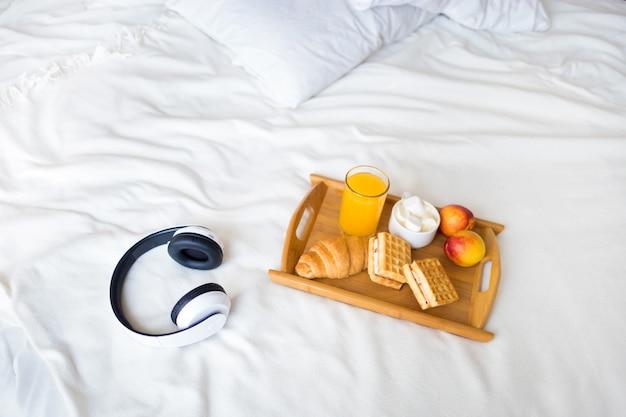 Café da manhã com croissant e café na cama branca Foto Premium