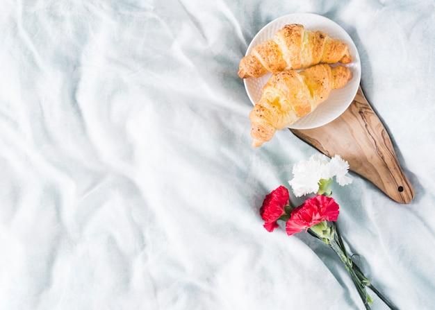 Café da manhã com croissant e flores Foto gratuita