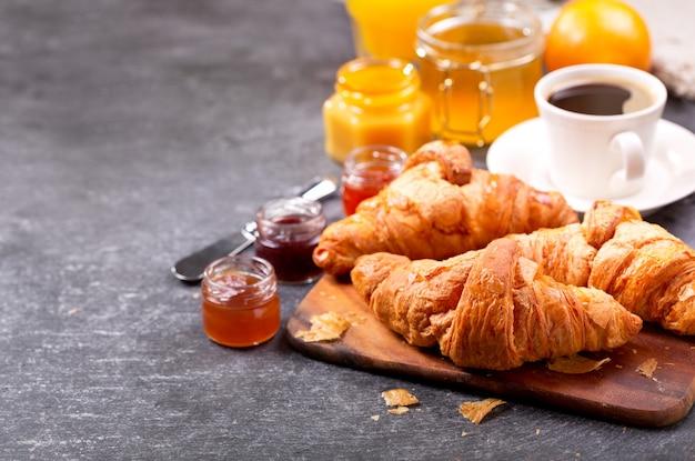 Café da manhã com croissants frescos e café na mesa escura Foto Premium