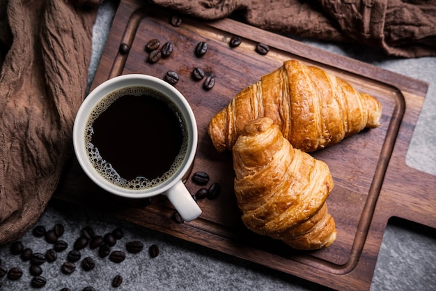 Café da manhã com croissants frescos e xícara de café preto na placa de madeira Foto Premium