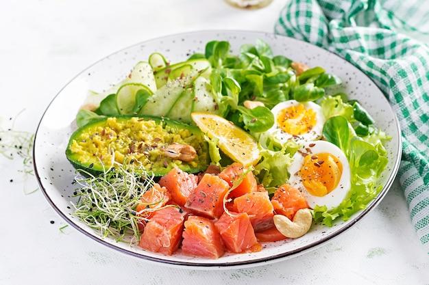 Café da manhã com dieta cetogênica. salada de salmão com verduras, pepinos, ovos e abacate. almoço keto / paleo. Foto gratuita