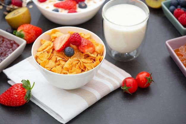 Café da manhã com flocos de milho misturados com grãos integrais e grupo de frutas Foto Premium