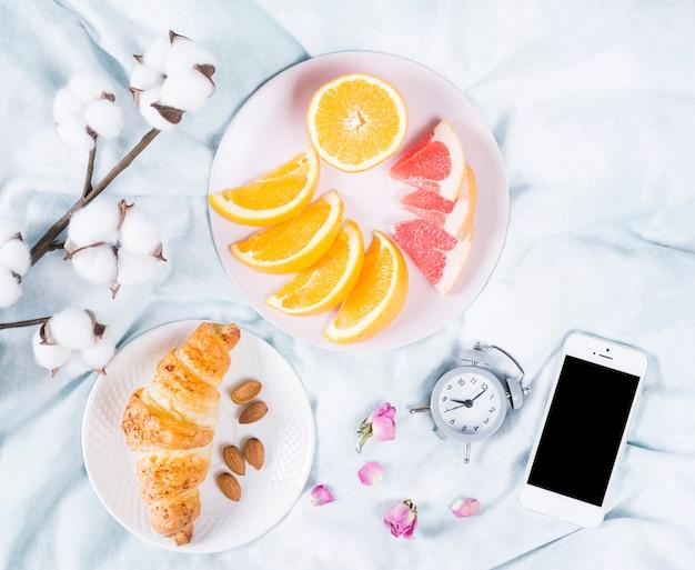 Café da manhã com frutas e telefone celular Foto gratuita