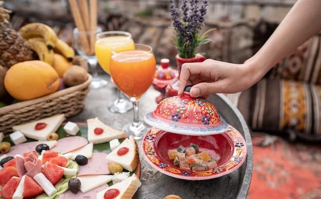 Café da manhã com grande paisagem no telhado da casa da caverna na cidade de goreme, na capadócia turquia. Foto Premium