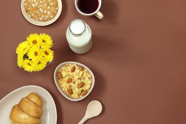 Café da manhã com leite, muesli e flores sobre fundo marrom Foto Premium