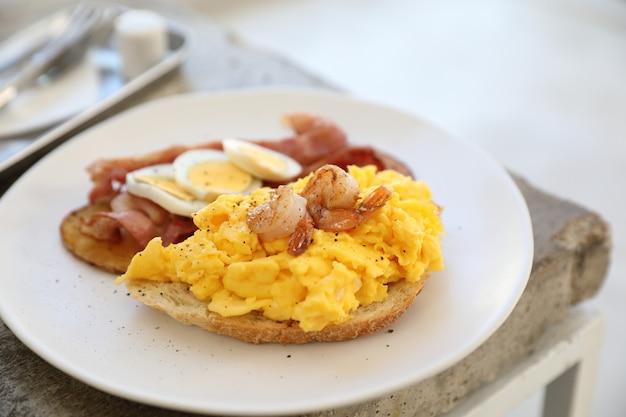 Café da manhã com ovos mexidos, batatas fritas, bacon e camarão Foto Premium