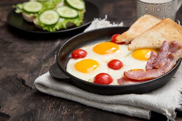Café da manhã com ovos, tomate cereja, bacon e torradas frescas torradas Foto Premium