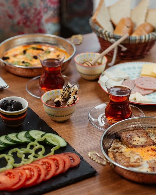 Café da manhã com várias comidas e chá preto Foto gratuita