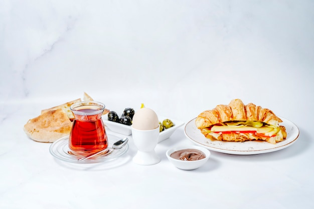 Café da manhã com vários alimentos e chá preto Foto gratuita