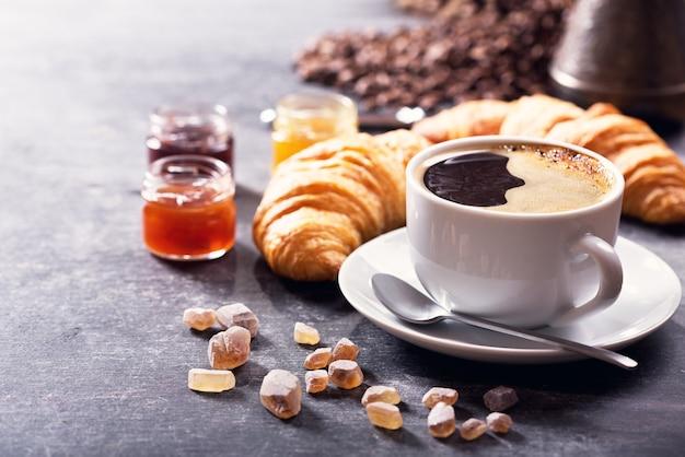 Café da manhã com xícara de café, croissant e geleia de frutas na mesa escura Foto Premium