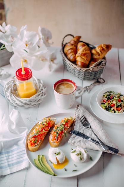 Café da manhã da noruega. torradas com salmão, ovos cozidos na mesa de madeira branca com salada, café, suco de laranja e croissants Foto Premium