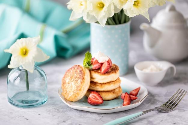 Café da manhã de primavera com flores, cheesecakes e frutas frescas Foto Premium