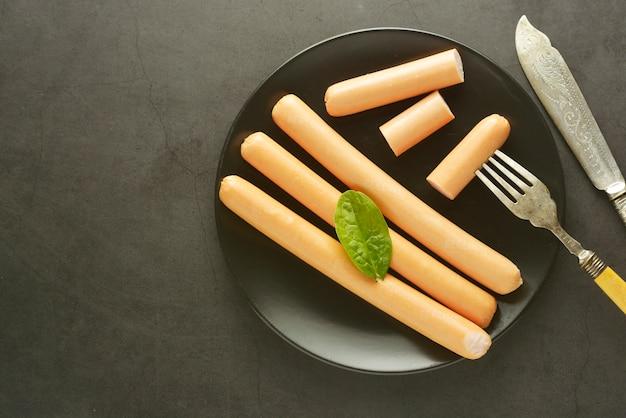 Café da manhã de salsichas de cachorro-quente de carne de frango cru fundo escuro Foto Premium
