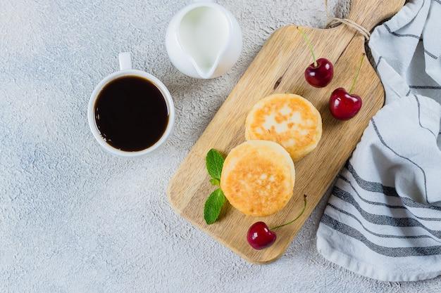 Café da manhã de verão com panquecas de queijo cottage, xícara de café preto, leite Foto Premium