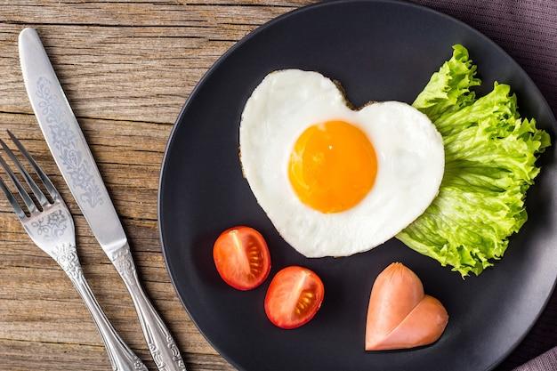 Café da manhã do dia dos namorados com ovos fritos em forma de coração servido no prato cinza. Foto Premium
