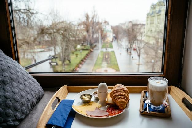 Café da manhã em uma mesa de madeira perto da janela Foto gratuita