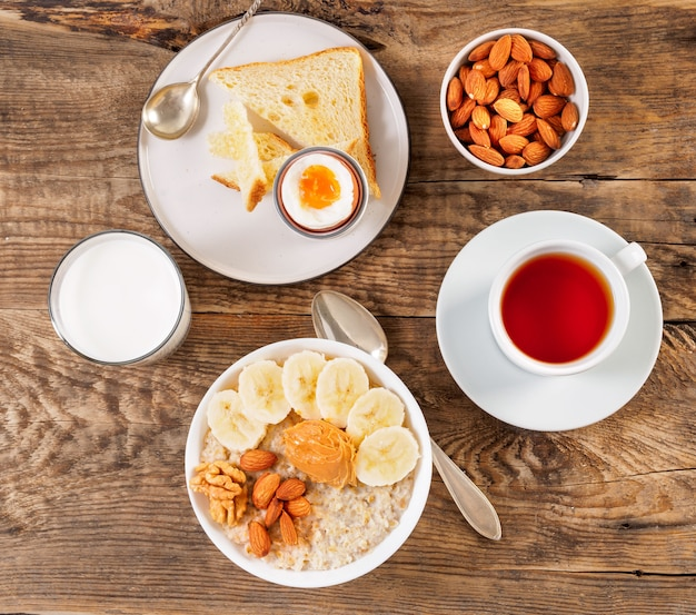 Café da manhã, em uma mesa de madeira, vista superior. um copo de leite, chá, aveia com Foto Premium