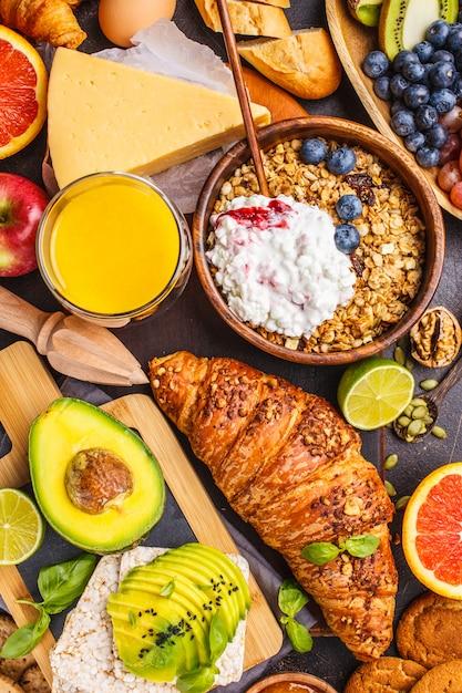 Café da manhã equilibrado saudável em um fundo escuro. muesli, leite, suco, croissants, queijo, biscoitos. Foto Premium