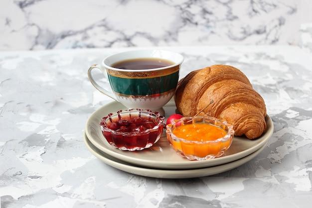 Café da manhã francês com croissants, geléia de damasco, geléia de cereja e uma xícara de chá, flores vermelhas e amarelas Foto gratuita