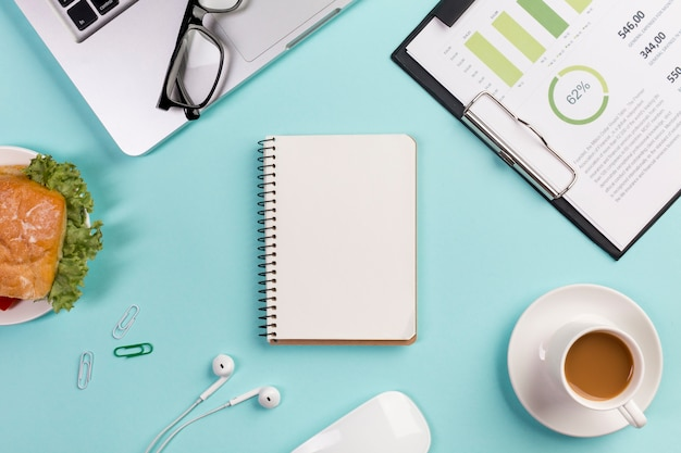 Café da manhã, gráfico de negócios, laptop, óculos, bloco de notas em espiral, fones de ouvido e mouse na mesa de escritório azul Foto gratuita