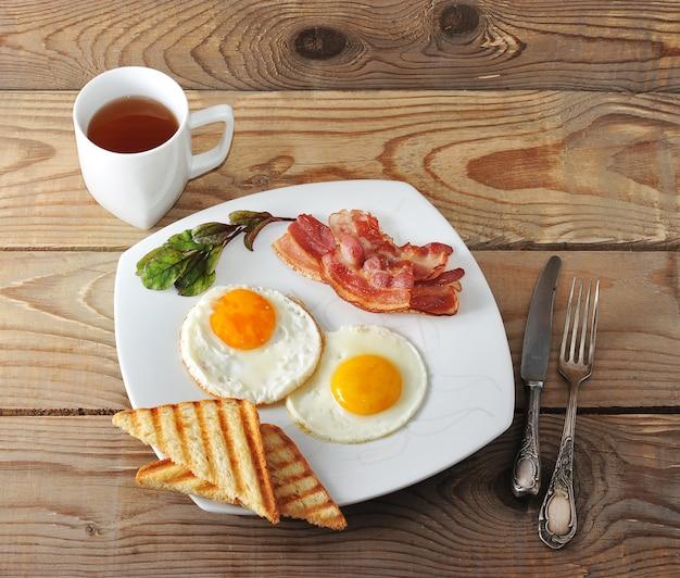 Café da manhã inglês com ovos mexidos, bacon, torradas fritas e chá Foto Premium