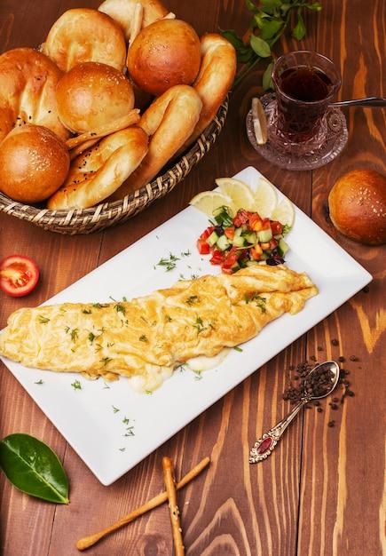 Café da manhã lanche crepes, omlettes com salada de legumes e pão pães em chapa branca Foto gratuita