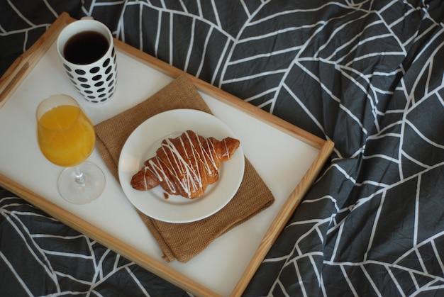 Café da manhã na cama. café, croissants e copo de suco de laranja. Foto Premium